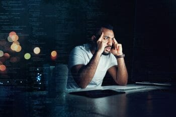Shot of a programmer looking stressed out while working on a computer code at night
