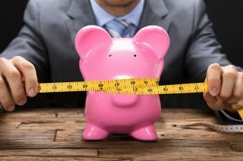 Midsection of businessman squeezing piggybank with tape measure on wooden table
