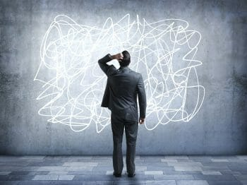 A confused businessman stares at a scribble design that is painted on a wall.  It represents the confusion and stress that some people feel in everyday life. He is looking up while standing with his back to the camera.