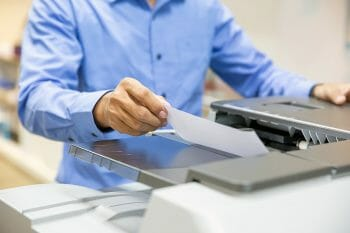 Businessmen Put the papers on the copier for copy and scanning documents papers in Office workplace.